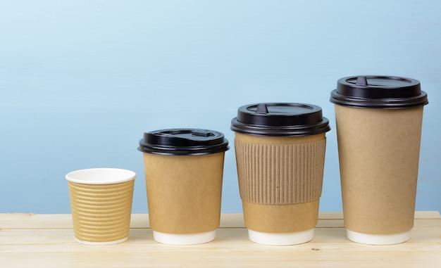 Ambachtelijke papieren koffiekopjes in de buurt van een lichtblauwe muur op een houten tafel