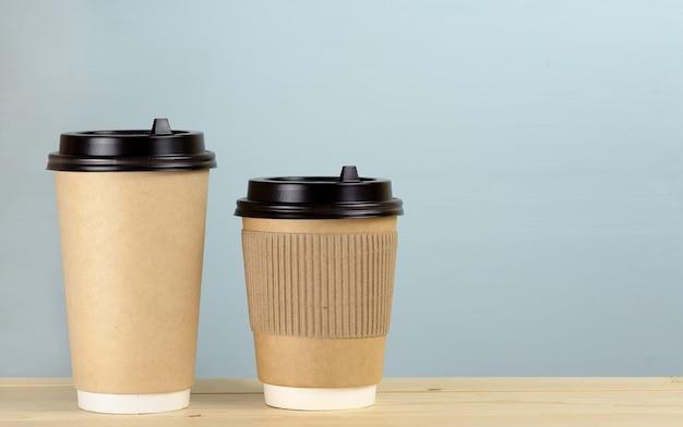 Ambachtelijke papieren koffiekopjes op een houten tafel in de buurt van een lichte muurachtergrond