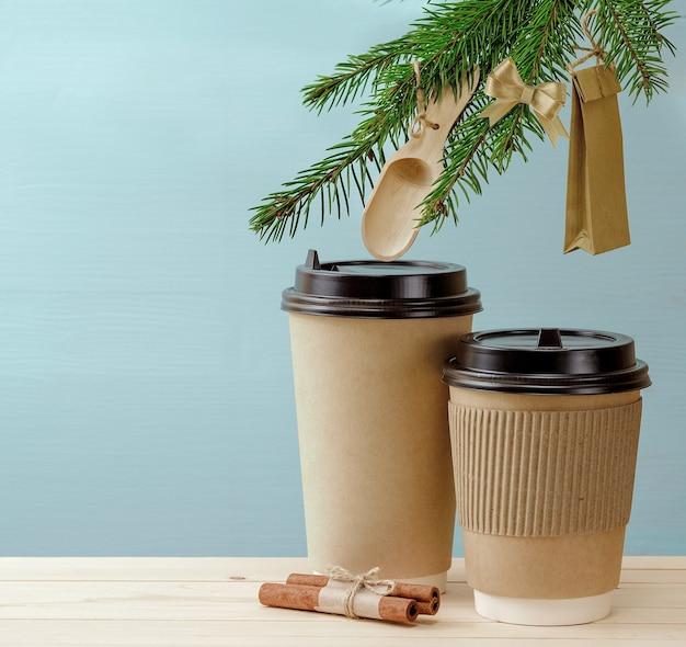 Ambachtelijke papieren koffiekopjes op een houten tafel met kerstversieringen op dennenboom. kerst koffie achtergrond