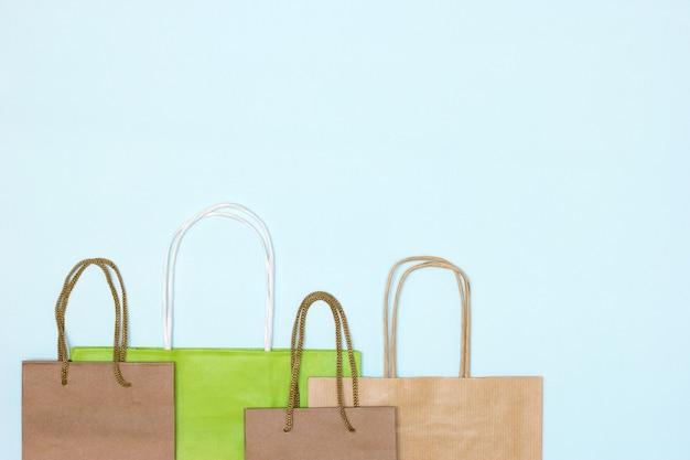 Ambachtelijke papieren merchandise tassen op pastelblauwe achtergrond. ruimte kopiëren. winkelen, verkoop minimaal concept