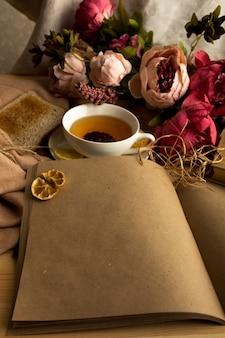 Ambachtelijke papieren notitie met kopje thee, bloemen en oude vintage klok