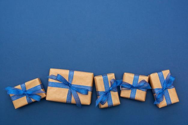 Ambachtelijke papieren verpakte geschenkdozen op een rij op blauw