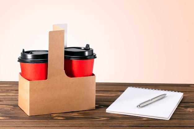 Ambachtelijke papieren zak met koffiekopjes op de houten tafel met kopie ruimte.