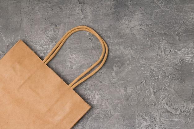 Ambachtelijke papieren zak op beton met kopie ruimte.