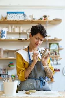 Ambachtelijke pottenbakkersvrouw bezig met creatief proces, gebruik gereedschap om vormklei te versieren en serviesgoed te vormen