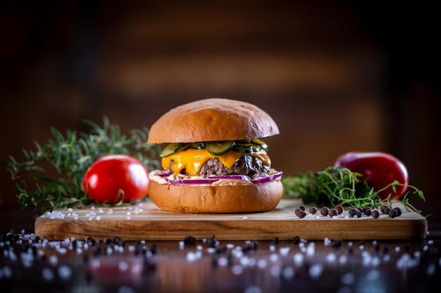Ambachtelijke rundvleesburger met cheddar, bacon, augurken, paarse ui en saus op houten achtergrond