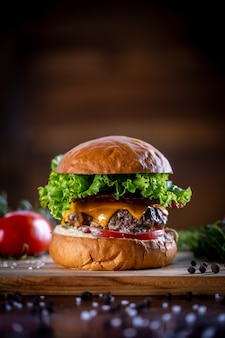 Ambachtelijke rundvleesburger met cheddar, bacon, sla en saus op houten achtergrond