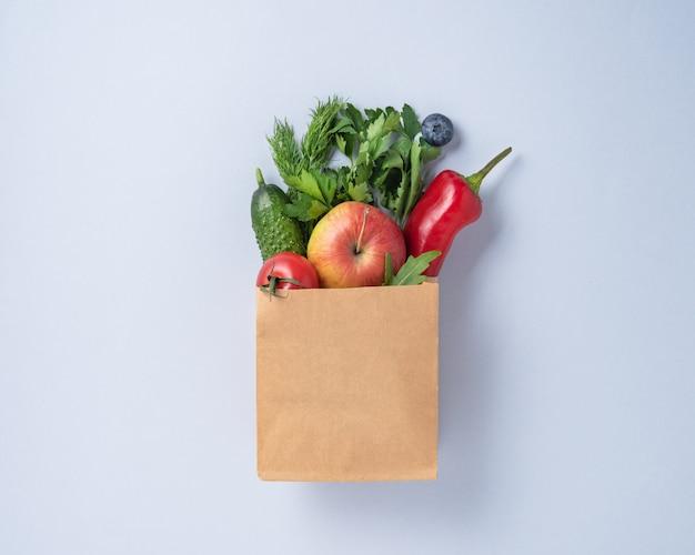 Ambachtelijke tas met verse groenten en fruit op blauwe achtergrond