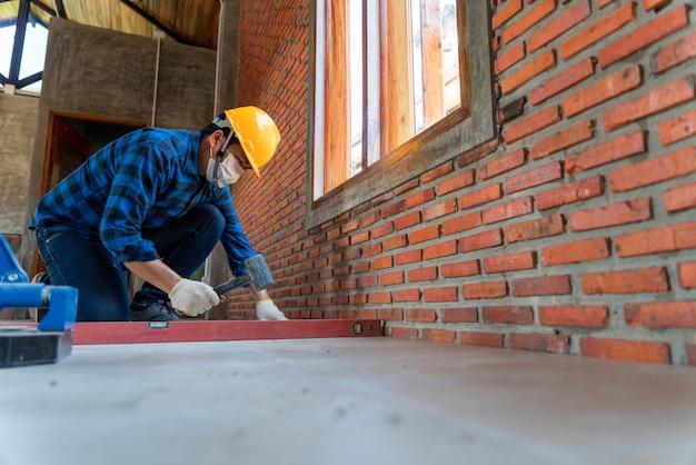 Ambachtelijke tegelzetterhanden werken aan een nieuwe huisingang, lokale en professionele klusjesman die tegels toepast op de bouwplaats