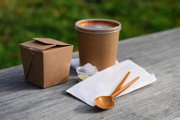 Ambachtelijke verpakking van aziatisch eten met lepels en servetten op een houten bankje.