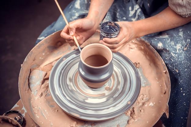 Ambachtelijke vrouw werkt met klei op een pottenbakkersschijf.