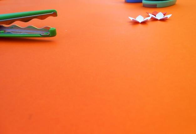 Ambachten met papieren bloemen en schaar op oranje achtergrond