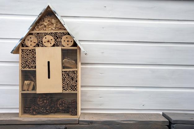 Ambachtsman bouwde een decoratief houten huis in een insectenhotel met compartimenten en natuurlijke componenten om lieveheersbeestjes en vlinders te beschermen en te promoten