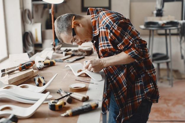 Ambachtsman die een houten plank snijdt