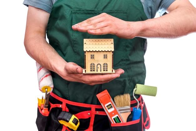 Ambachtsman die houten huismodel geïsoleerd houdt