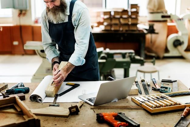 Ambachtsman die in een houten winkel werkt