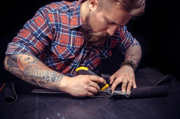 Ambachtsman die in zijn atelier een nieuwe leerproductie vormt.