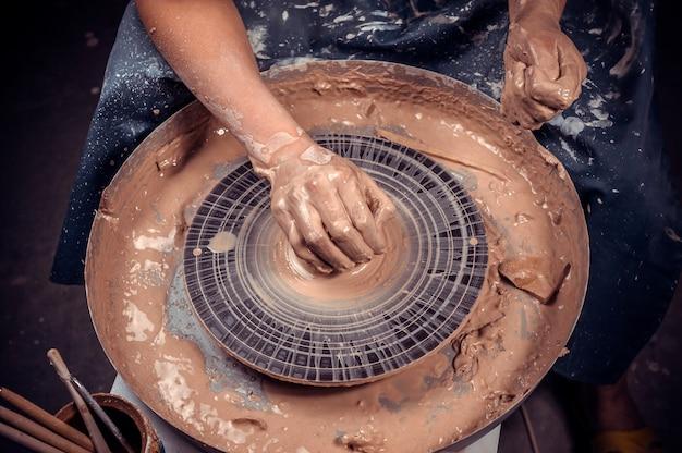 Ambachtsman laat zien hoe te werken met klei en aardewerkschijf. het concept van ambachtelijke creativiteit. detailopname.