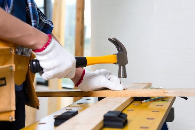 Ambachtsman met hamer gespijkerd in werkplaats, timmerman met hamer sloeg een spijker voor montage hout in een timmerwerkplaats