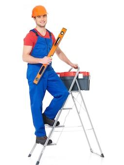 Ambachtsman met tools met trappen, volledig portret op wit
