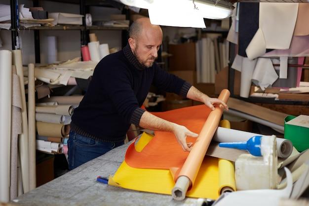 Ambachtsman snijden leer met cutter in werkplaats