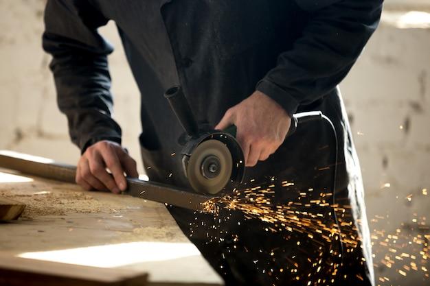 Ambachtsman werken met elektrisch gereedschap in de werkplaats