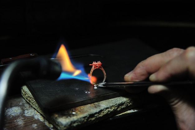 Ambachtsman werkt met behulp van een gasspuitgereedschap om een ring te maken