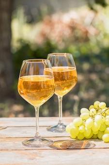 Amberwijn in glazen over de aard: stilleven met kaas, druiven en wijn in een rustieke stijl. georgische nationale wijn of italiaanse wijn passito