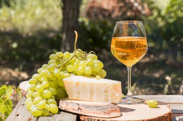 Amberwijn in glazen over de aard: stilleven met kaas, druiven en wijn in een rustieke stijl. georgische nationale wijn of italiaanse wijn