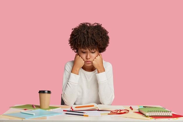 Ambitieus studentenmeisje dat zich voordeed aan het bureau tegen de roze muur