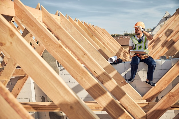 Ambitieuze architect die zijn beschermende helm aanraakt terwijl hij een klembord vasthoudt en op een bouwplaats zit