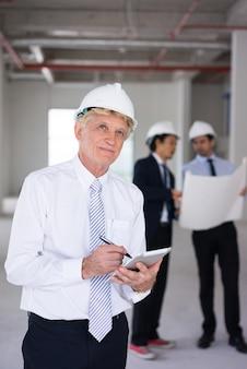 Ambitieuze architect in bouwvakker die bouwterrein bekijkt en aan ontwerp denkt.