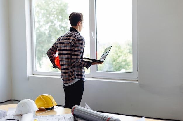 Ambitieuze architect met een laptop die door een raam kijkt
