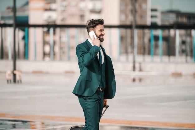 Ambitieuze blanke bebaarde zakenman in pak met behulp van slimme telefoon en bagage te dragen tijdens het wakker worden op de parkeerplaats. bedrijfsconcept reis. kijk niet achterom, zo ga je niet.
