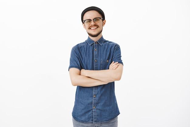 Ambitieuze creatieve en knappe vriendelijk ogende volwassen man met snor in zwarte muts en bril hand in hand gekruist op de borst met zelfverzekerde en zelfverzekerde glimlach poseren