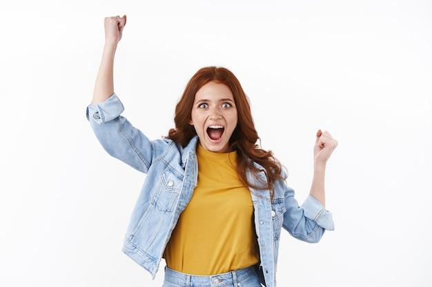 Ambitieuze en gemotiveerde schattige roodharige vrouw in spijkerjasje, handen omhoog in hoera-gebaar, vuistpomp triomfantelijk schreeuwend, glimlachend geamuseerd staren verbaasd wroeten naar favoriet team, witte muur