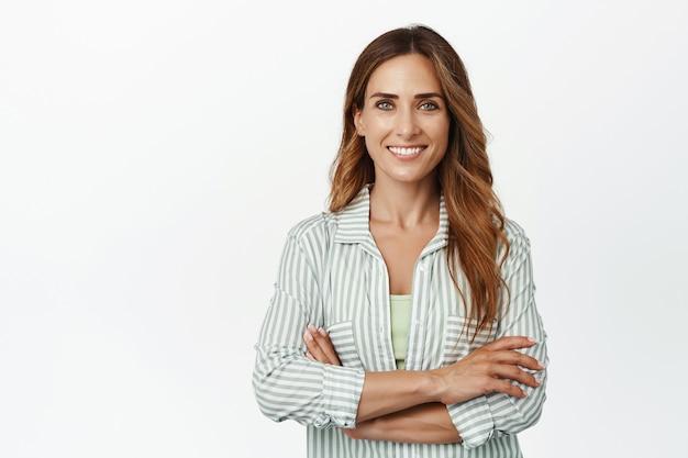 Ambitieuze en zelfverzekerde zakenvrouw die met gekruiste armen staat en zelfverzekerd naar voren glimlacht