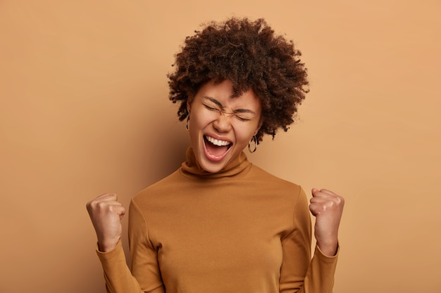 Ambitieuze gelukkige triomfantelijke vrouw viert geweldige overwinning met beide gebalde vuisten, hoort uitstekend nieuws, roept positief hoera