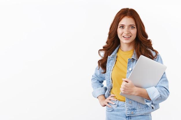 Ambitieuze schattige vrouwelijke student werkt freelance op afstand om collegegeld te betalen, laptop in de arm te houden, hand op taille te leggen professionele zelfverzekerde pose, glimlachend gemotiveerd, ga naar caféwerk