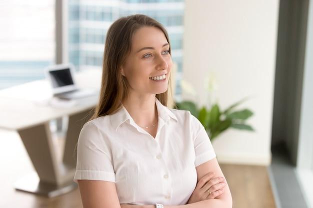 Ambitieuze zakenvrouw met gekruiste armen kijkt uit naar de toekomst