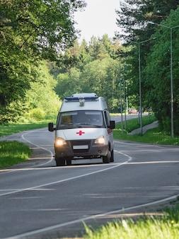 Ambulance in beweging op een bosweg