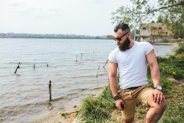 American bearded man kijkt op de oever van de rivier in een blauwe jas