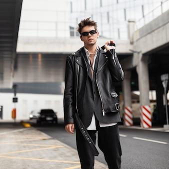 American fashion jongeman model in een stijlvolle oversized leren zwarte jas in donkere zonnebril in vintage jeans loopt op straat in de stad. trendy knappe hipster man staat in de buurt van de weg buiten.
