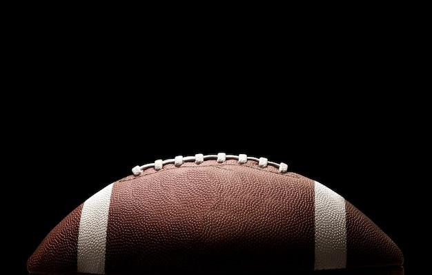 American football bal op zwarte achtergrond verlicht door het licht