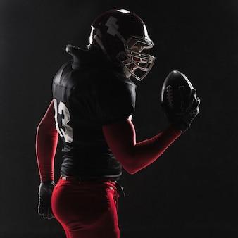 American football-speler poseren met bal op zwarte achtergrond