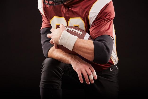 American football-speler zit in een positie van paraatheid, handen om een mache op een zwarte achtergrond, concept te houden
