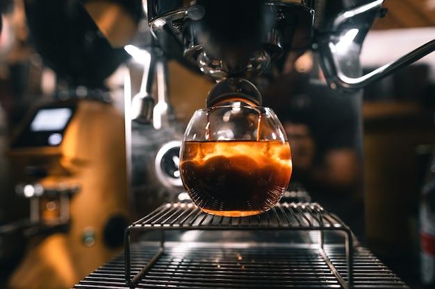 Americano koffie in een mok uit de machine, de koffiedruppel om het water in een glas te mengen.