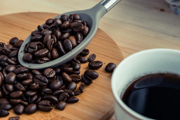 Americano-koffiekop met geroosterde koffieboon in lepelplaats op de houten lijst