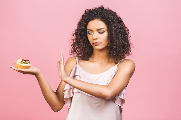 Amerikaans afro-meisje eet geen cake. conceptie om af te vallen. hand gebaren nee tegen een cake. geïsoleerd op roze achtergrond.