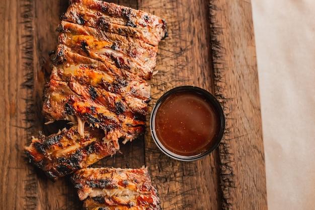 Amerikaans barbecuevlees heerlijke bbq-ribben gesneden op houten bureau gegrilde ribeye steak vlees griling s